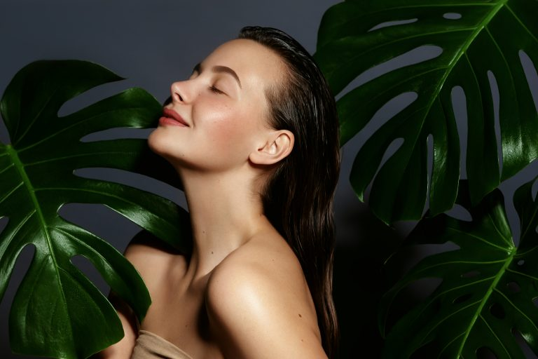 Hydrated skin .Beautiful young woman portrait with fresh green exotic tropical leafs.